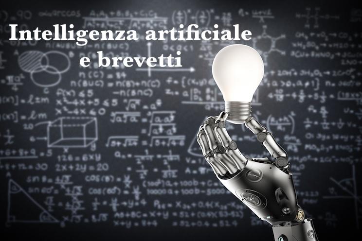 """Illustrazione raffigurante mano di robot umanoide in primo piano, sulla destra, mentre regge una lampadina accesa, su sfondo costituito da una lavagna nera con scritte che ritraggono numeri, forme geometriche e formule matematiche - a esprimere il concetto di invenzione legato all'intelligenza artificiale - e scritta bianca """"Intelligenza artificiale e brevetti""""."""
