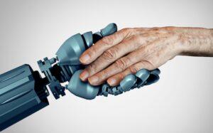Primo piano di mano di robot umanoide che stringe la mano di un anziano su sfondo bianco, a esprimere il concetto di intelligenza artificiale per assistenza anziani.